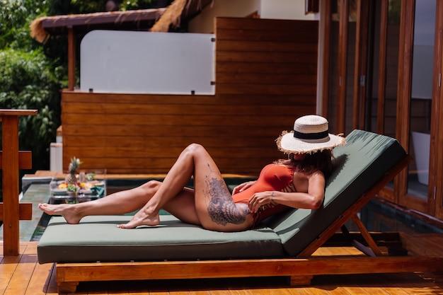 맞는 완벽한 검게 그을린 바디 브론즈 피부를 가진 예쁜 여자는 밀짚 모자 커버 얼굴이있는 원피스 수영복에 럭셔리 열대 빌라에서 녹색 sunbed에 놓여 있습니다.