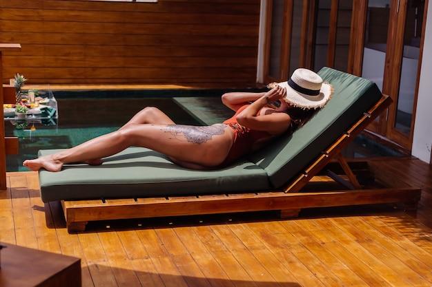 完璧な日焼けしたボディのブロンズ肌にぴったりのきれいな女性が、麦わら帽子のカバーフェイスを備えたワンピース水着の豪華なトロピカルヴィラの緑のサンベッドに横たわっています。