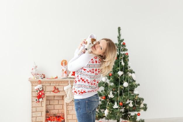 クリスマスツリーの背景に面白い子犬ジャックラッセルテリアときれいな女性