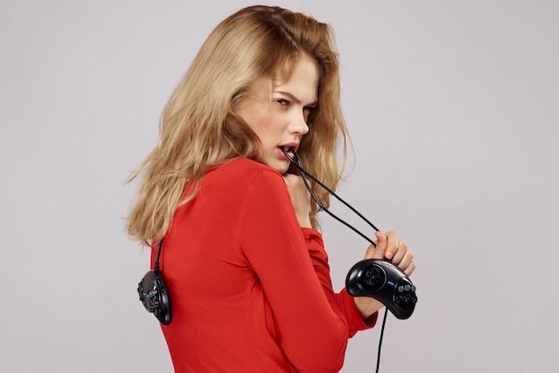 Красивая женщина с геймпадами, играющими на консоли