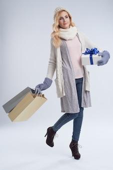 Donna graziosa con i regali che posano contro il fondo bianco