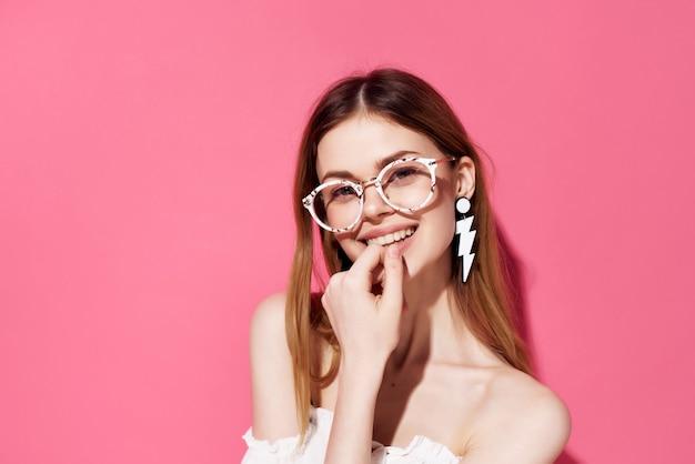 Красивая женщина с очками серьги мода розовый фон