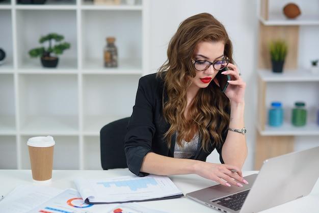 ビジネス電話での会話を持つメガネのきれいな女性