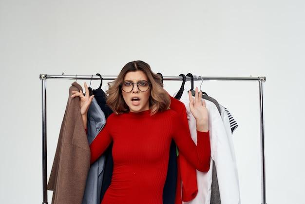 Красивая женщина в очках рядом с одеждой мода весело изолированный фон