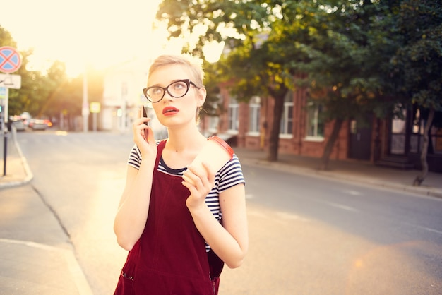 夏に電話で話している通りで眼鏡をかけたきれいな女性
