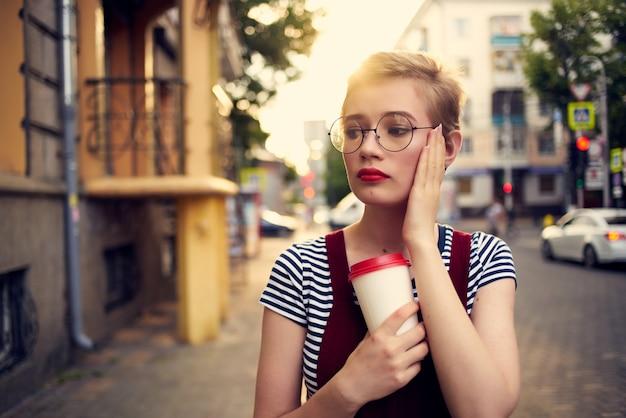 通りで眼鏡をかけたきれいな女性が一杯のコーヒーを歩く