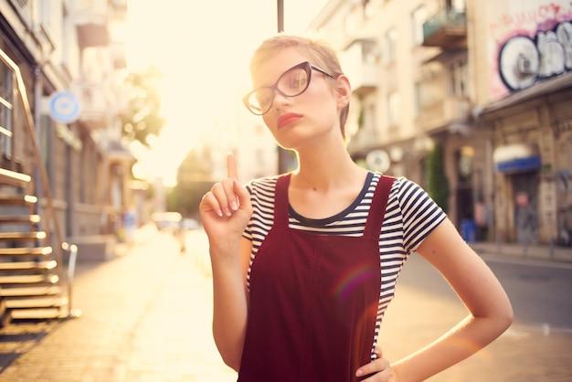 眼鏡をかけたきれいな女性が屋外で一杯のコーヒーウォーク。高品質の写真