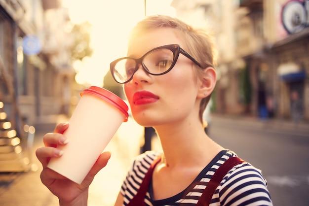 屋外で眼鏡をかけたきれいな女性一杯のコーヒーウォーク