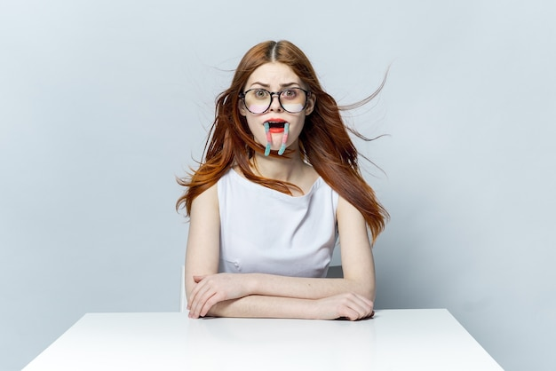テーブルの感情のアンティックに座っている眼鏡をかけたきれいな女性