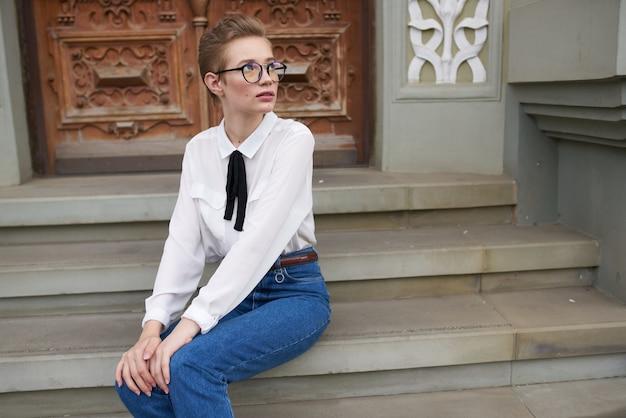 책 생활 방식으로 도시를 산책하는 안경을 쓴 예쁜 여자