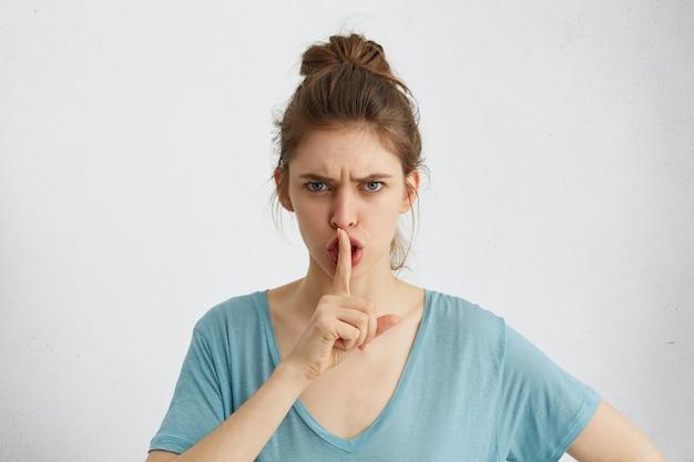 うるさい雰囲気に悩まされている人からの沈黙を要求する不満で眉を眉をひそめている悲観的な表情のきれいな女性。