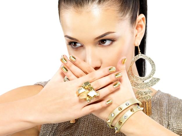 Красивая женщина с золотыми гвоздями и красивыми золотыми украшениями на белом фоне
