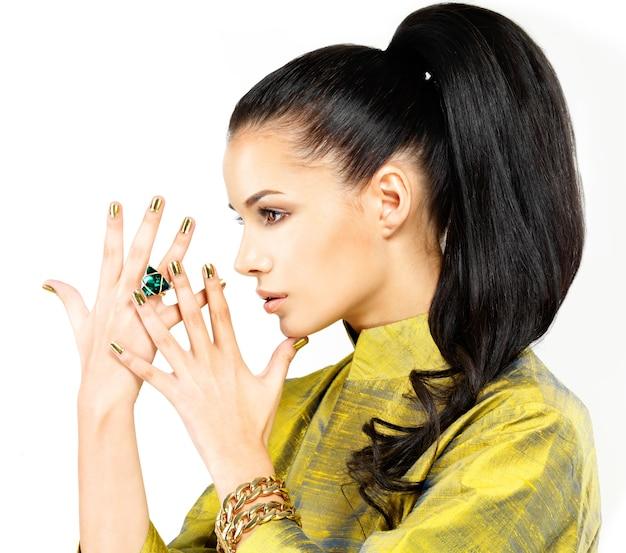 Красивая женщина с золотыми ногтями и красивый драгоценный камень изумруд - изолированные на белом фоне