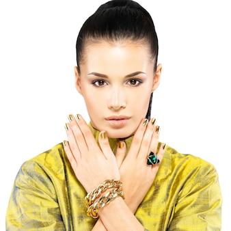 金色の爪と美しい宝石のエメラルドを持つきれいな女性