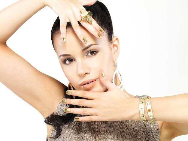 Bella donna con chiodi d'oro e bellissimi gioielli in oro isolati su sfondo bianco