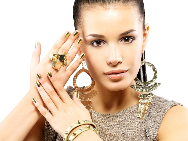 Bella donna con chiodi d'oro e bellissimi gioielli d'oro isolati sul muro bianco