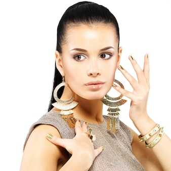 Pretty woman with golden nails and beautiful gold jewelry isolated on white wall