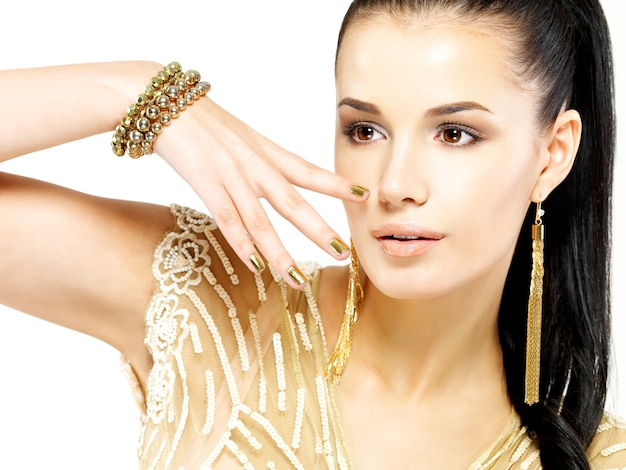 Pretty woman with golden nails and beautiful gold jewelry isolated on white