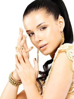 Bella donna con chiodi d'oro e splendidi gioielli in oro isolati su bianco