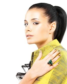 Bella donna con unghie d'oro e bella pietra preziosa smeraldo