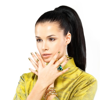 Pretty woman with golden nails and beautiful precious stone emerald