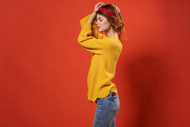 ヘッドバンド黄色のセーターの手のジェスチャーのポーズできれいな女性