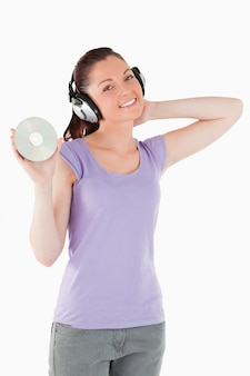 Pretty woman with headphones holding a cd while standing
