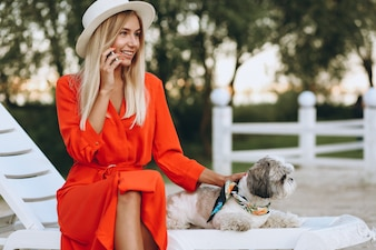 Pretty woman with her cute dog on vacation