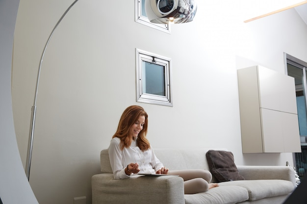Pretty woman with laptop on sofa