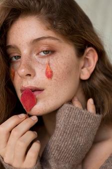彼女の顔に葉を持つきれいな女性