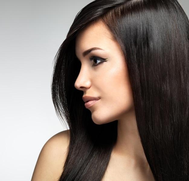 긴 갈색 머리카락을 가진 예쁜 여자. 패션 모델 포즈의 프로필 초상화