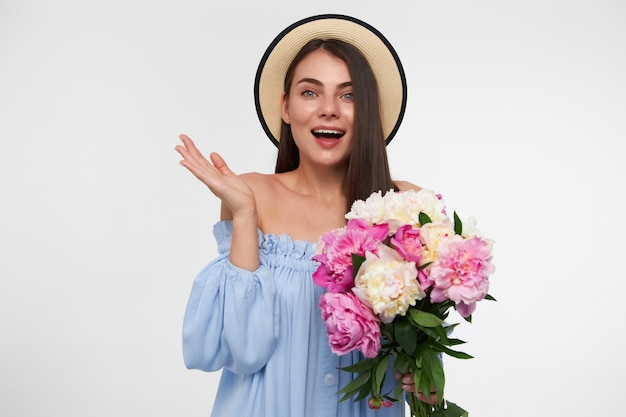 Pretty woman with long brunette hair. wearing a hat and blue dress. holding bouquet of flowers and and showing surprised reaction