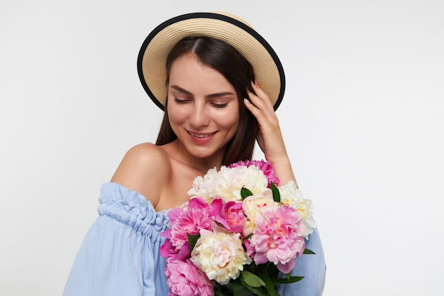 Pretty woman with long brunette hair. wearing a hat and blue dress. holding bouquet of flowers and touching her hair