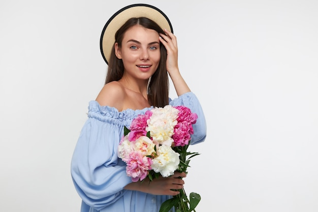 Pretty woman with long brunette hair. wearing a hat and blue pretty dress. holding a bouquet of beautiful flowers and touching hair