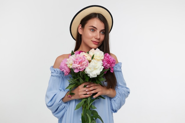 Pretty woman with long brunette hair. wearing a hat and blue pretty dress. holding a bouquet of beautiful flowers