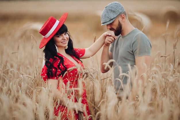 Красивая женщина с длинными темными волнистыми волосами в красном платье с красивым мужчиной в серой футболке