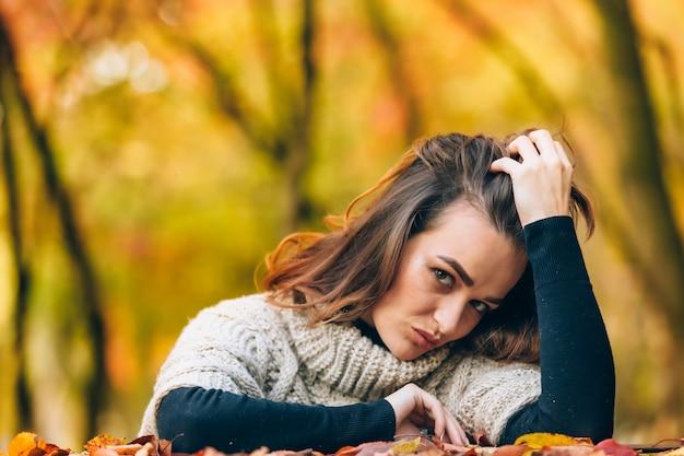 Красивая женщина с роскошными волосами кладет голову на руку на фоне осеннего парка. крупный план
