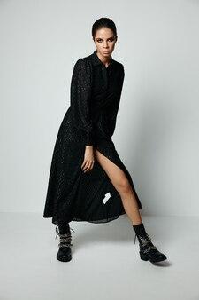 ブーツと黒のファッショナブルなドレスで彼女の顔に化粧をしているきれいな女性