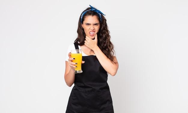 Красивая женщина с широко открытыми глазами и ртом, положив руку на подбородок и держа стакан апельсинового сока