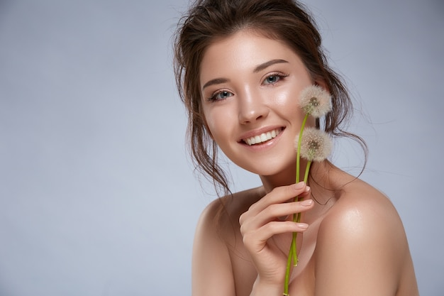 Красивая женщина с естественным макияжем и обнаженными плечами держит одуванчики и улыбается