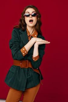 スーツファッション服赤い背景で口を開けてきれいな女性