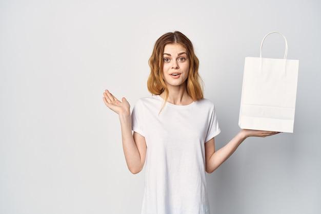 手にパッケージを持ったきれいな女性のモックアップショッピング。高品質の写真