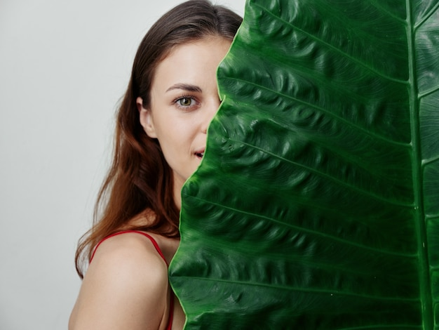 ヤシの葉の半分の顔の明るい背景を持つきれいな女性