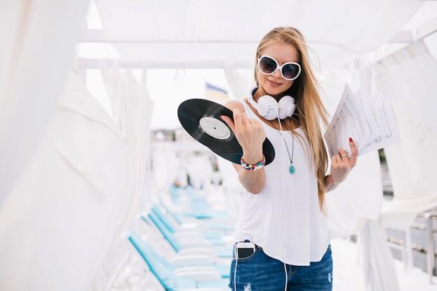 Красивая женщина с бумагами и виниловыми пластинками