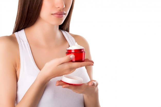 Pretty woman with perfect skin holding a tube with face cream. young girl with hands on the front. red jar of cream. close-up.. beautiful woman wearing a face and hands cream.