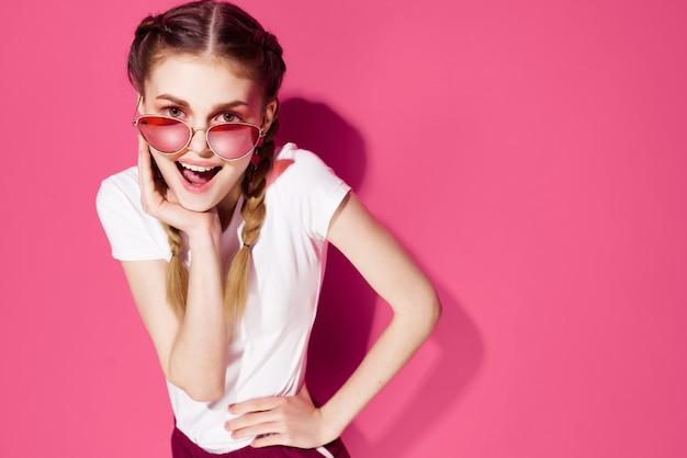 Pretty woman with pigtails wearing sunglasses pink background street style