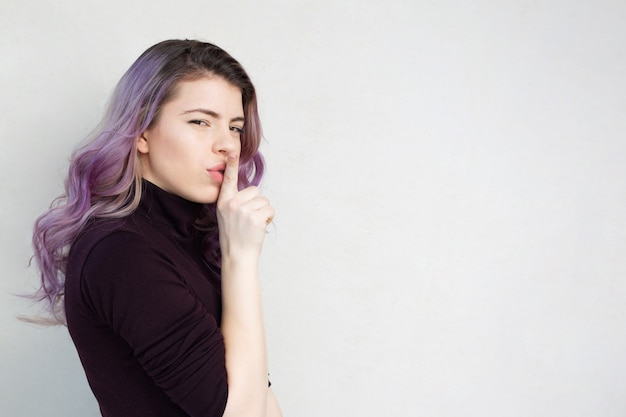 Pretty woman with purple hair showing silence gesture. empty space