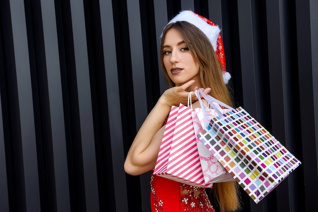 Pretty woman with in red dress holding gift bags. new year and christmas gifts concept
