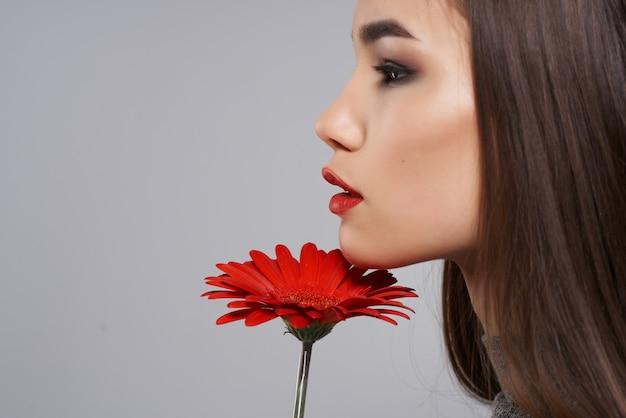 赤い花のギフト化粧品モデルを持つきれいな女性