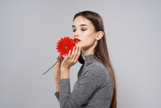 Pretty woman with red flower gift cosmetics model